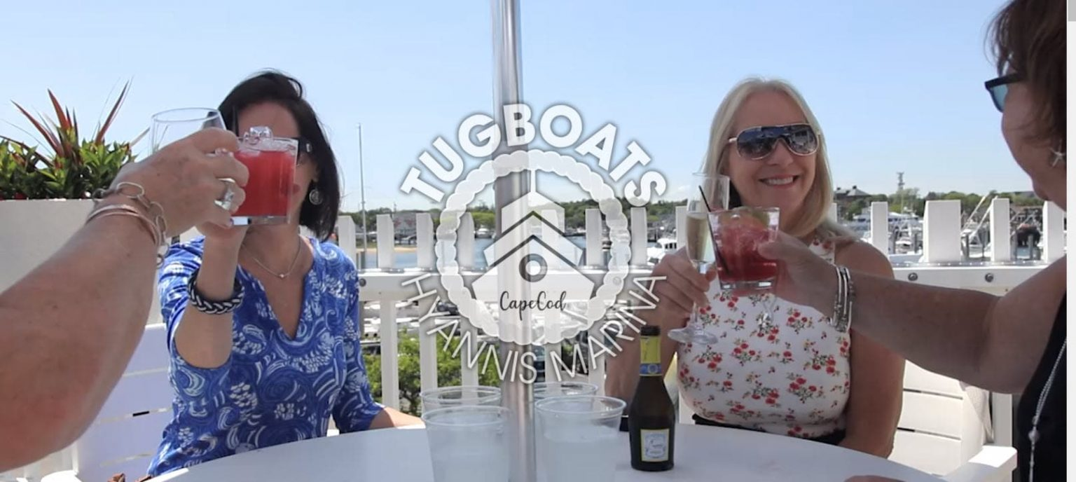 2 women having drinks on the deck at Tugboats